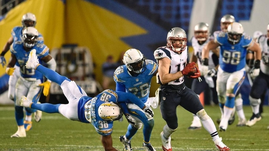 New England Patriots wide receiver Julian Edelman (11) pulls free from San Diego Chargers cornerback Brandon Flowers (26) and strong safety Marcus Gilchrist (38) as he runs for a touchdown against the San Diego Chargers during the second half in an NFL football game Sunday, Dec. 7, 2014, in San Diego. (AP Photo/Denis Poroy)