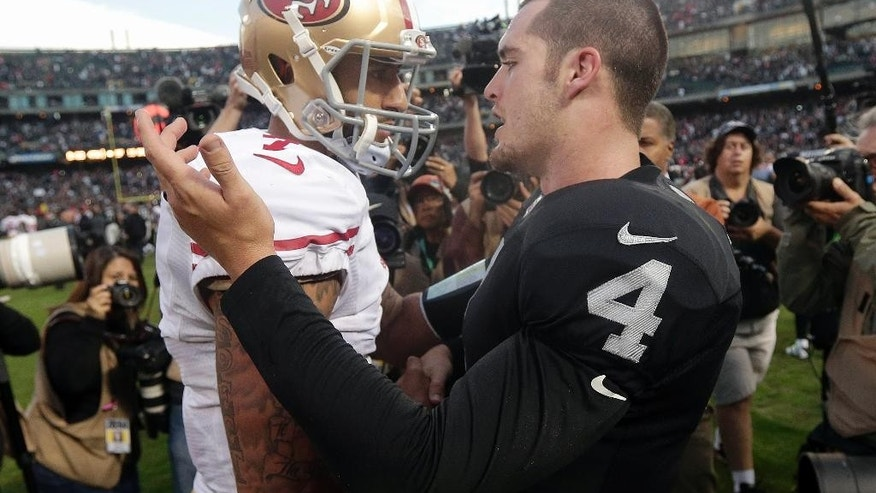Oakland Raiders quarterback Derek Carr (4) greets San Francisco 49ers quarterback Colin Kaepernick (7) after an NFL football game in Oakland, Calif., Sunday, Dec. 7, 2014. The Raiders won 24-13. (AP Photo/Marcio Jose Sanchez)
