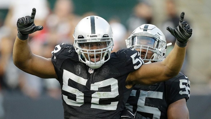 Oakland Raiders outside linebacker Khalil Mack (52) celebrates after sacking San Francisco 49ers quarterback Colin Kaepernick with outside linebacker Sio Moore during the fourth quarter of an NFL football game in Oakland, Calif., Sunday, Dec. 7, 2014. The Raiders won 24-13. (AP Photo/Ben Margot)
