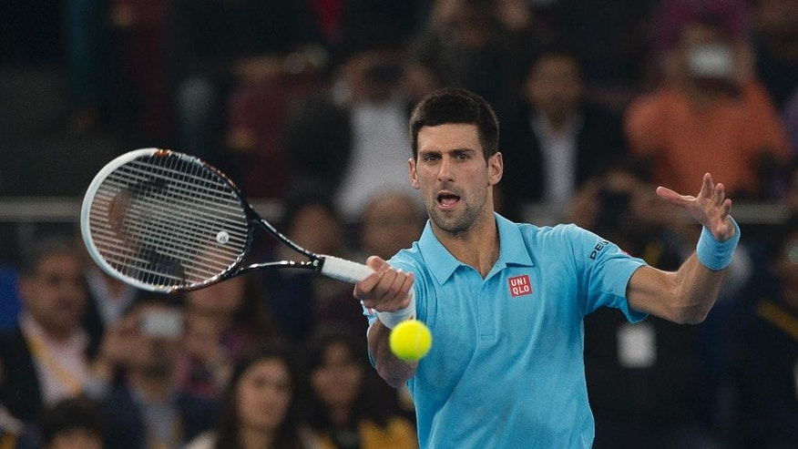 Musafir.com UAE Royals Novak Djokovic returns a ball to Micromax Indian Aces player Roger Federer during the International Premier Tennis League, in New Delhi, India, Monday, Dec. 8, 2014. (AP Photo/Manish Swarup)