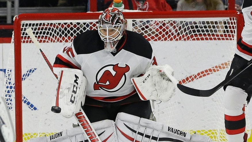 New Jersey Devils goalie Cory Schneider deflects a shot on goal during the first period of an NHL hockey game against the Carolina Hurricanes in Raleigh, N.C., Monday, Dec. 8, 2014. (AP Photo/Gerry Broome)