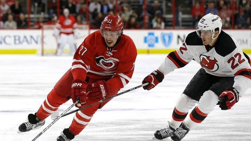Carolina Hurricanes' Justin Faulk (27) skates as New Jersey Devils' Eric Gelinas (22) defends during the second period of an NHL hockey game in Raleigh, N.C., Monday, Dec. 8, 2014. (AP Photo/Gerry Broome)
