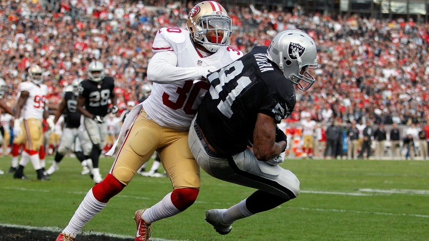 OAKLAND, CA - DECEMBER 07:  Mychal Rivera #81 of the Oakland Raiders scores a touchdown in the fourth quarter in front of Leon McFadden #30 of the San Francisco 49ers  at O.co Coliseum on December 7, 2014 in Oakland, California.  (Photo by Brian Bahr/Getty Images)