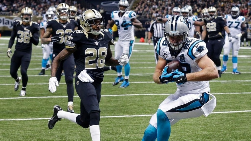 Carolina Panthers tight end Greg Olsen (88) pulls in a touchdown reception in front of New Orleans Saints cornerback Keenan Lewis (28) in the first half of an NFL football game in New Orleans, Sunday, Dec. 7, 2014. (AP Photo/Bill Feig)