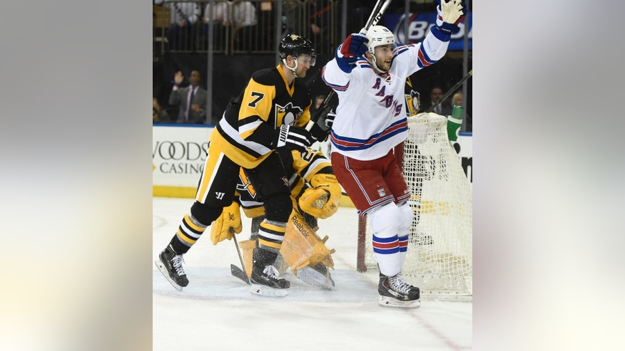 New York Rangers center Derick Brassard (16) celebrates the goal scored by  left wing Rick Nash as Pittsburgh Penguins defenseman Paul Martin (7) reacts in the second period of an NHL hockey game at Madison Square Garden on Monday, Dec. 8, 2014, in New York. (AP Photo/Kathy Kmonicek)