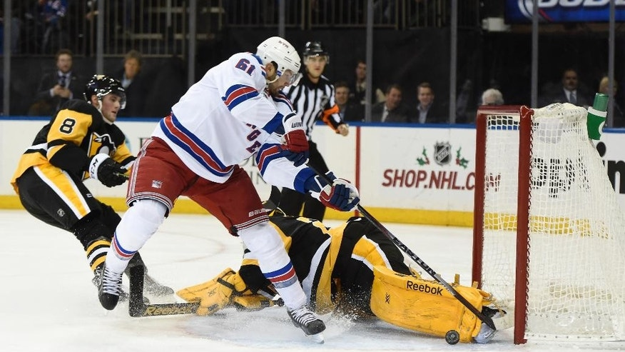 New York Rangers left wing Rick Nash (61) shoots the puck past Pittsburgh Penguins goalie Marc-Andre Fleury (29) to score as  Penguins defenseman Brian Dumoulin (8) looks on in the second period of an NHL hockey game at Madison Square Garden on Monday, Dec. 8, 2014, in New York. (AP Photo/Kathy Kmonicek)