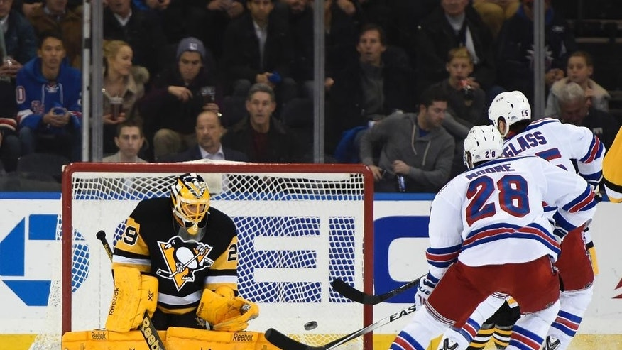 Pittsburgh Penguins goalie Marc-Andre Fleury (29) defends the net against  New York Rangers center Dominic Moore (28) and left wing Tanner Glass (15) in the first period of an NHL hockey game at Madison Square Garden on Monday, Dec. 8, 2014, in New York. (AP Photo/Kathy Kmonicek)