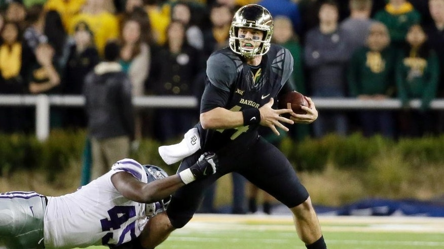 Kansas State defensive end Marquel Bryant (45) is unable to stop Baylor quarterback Bryce Petty (14) from rolling out of the pocket before passing in the second half of an NCAA college football game, Saturday, Dec. 6, 2014, in Waco, Texas. Baylor won 38-27. (AP Photo/Tony Gutierrez)