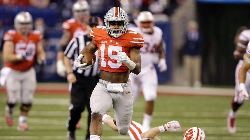 Ohio State running back Ezekiel Elliott loses his shoe as he runs for a 60-yard gain during the second half of the Big Ten Conference championship NCAA college football game against Wisconsin Saturday, Dec. 6, 2014, in Indianapolis. (AP Photo/Darron Cummings)