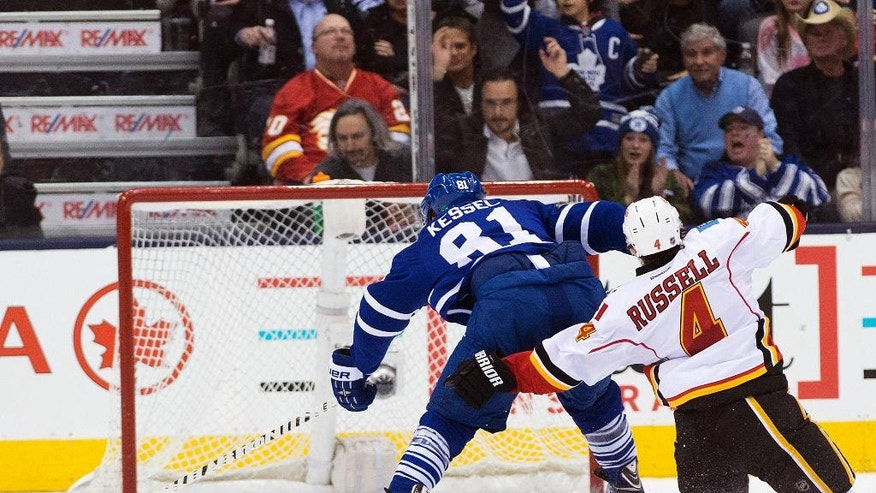 Toronto Maple Leafs forward Phil Kessel (81) fights off Calgary Flames defenseman Kris Russell (4) to score an empty-net goal during the third period of an NHL hockey game in Toronto on Tuesday, Dec. 9, 2014. (AP Photo/The Canadian Press, Nathan Denette)