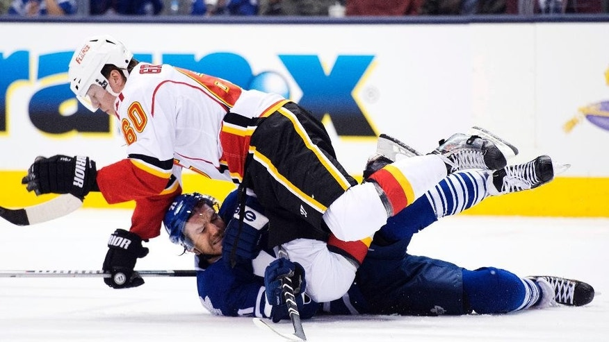 Toronto Maple Leafs forward David Clarkson, bottom, gets taken out by Calgary Flames forward Markus Granlund, top, during the first period of an NHL hockey game in Toronto on Tuesday, Dec. 9, 2014. (AP Photo/The Canadian Press, Nathan Denette)