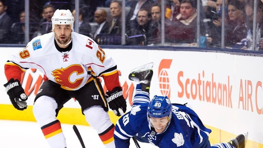 Toronto Maple Leafs forward David Booth (20) gets tripped up by Calgary Flames defenseman Deryk Engelland (29) during the second period of an NHL hockey game in Toronto on Tuesday, Dec. 9, 2014. (AP Photo/The Canadian Press, Nathan Denette)