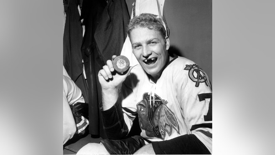FILE - In this March 25, 1962, file photo Bobby Hull of the Chicago Blackhawks holds puck which he drove into the New York Rangers' net to score his 50th goal of the season at New York's Madison Square Garden. The Gordie Howe hat trick to this day means a goal, an assist, and a fight in the same game. (AP Photo/File)