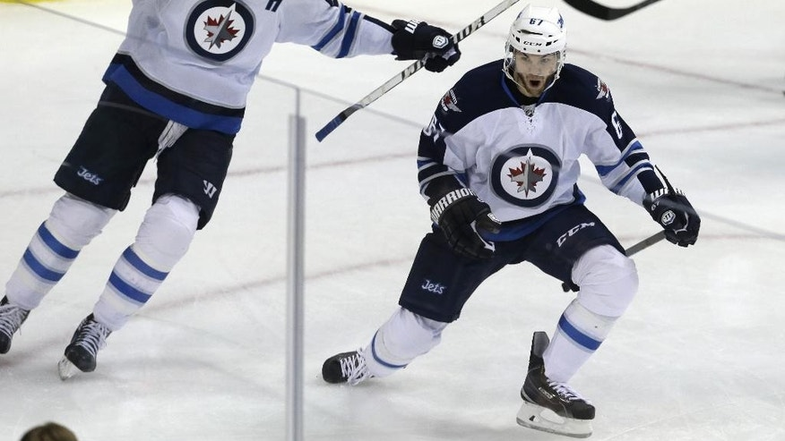 Winnipeg Jets right wing Michael Frolik celebrates scoring a goal with teammate Blake Wheeler (26) during the second period of an NHL hockey game Tuesday, Dec. 9, 2014, in Dallas. The Jets won 5-2. (AP Photo/LM Otero)