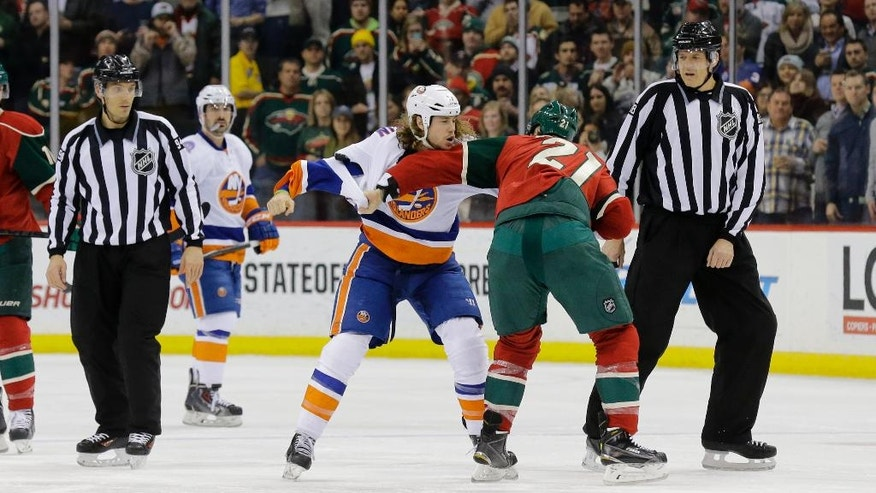 New York Islanders left wing Matt Martin, left, fights with Minnesota Wild center Kyle Brodziak (21) during the second period of an NHL hockey game in St. Paul, Minn., Tuesday, Dec. 9, 2014. (AP Photo/Ann Heisenfelt)
