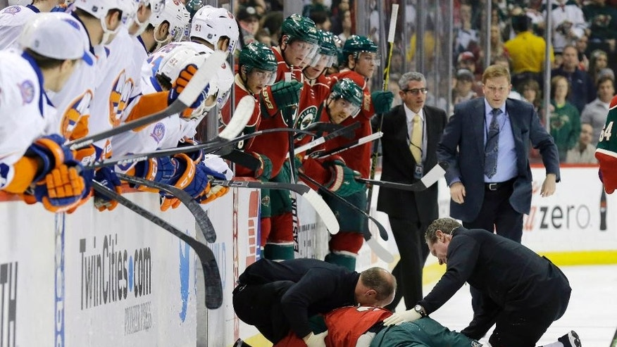 Medical personnel tend to Minnesota Wild defenseman Keith Ballard after he was injured on a check into the boards by New York Islanders left wing Matt Martin during the second period of an NHL hockey game in St. Paul, Minn., Tuesday, Dec. 9, 2014. (AP Photo/Ann Heisenfelt)
