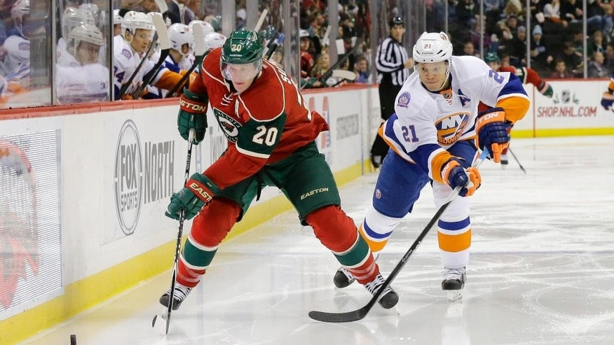 Minnesota Wild defenseman Ryan Suter (20) and New York Islanders right wing Kyle Okposo (21) chase the puck during the second period of an NHL hockey game in St. Paul, Minn., Tuesday, Dec. 9, 2014. (AP Photo/Ann Heisenfelt)