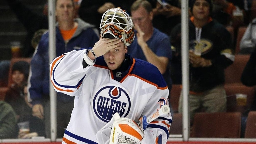 Edmonton Oilers goalie Viktor Fasth, of Sweden, wipes his face after giving up a goal to Anaheim Ducks' Ryan Kesler during the second period of an NHL hockey game Wednesday, Dec. 10, 2014, in Anaheim, Calif. (AP Photo/Jae C. Hong)