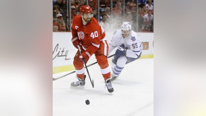 Detroit Red Wings left wing Henrik Zetterberg (40) of Sweden controls the puck and temporarily sprays Toronto Maple Leafs defenseman Korbinian Holzer (55) of Germany with ice, during the second period of an NHL hockey game in Detroit, Wednesday, Dec. 10, 2014. (AP Photo/Carlos Osorio)