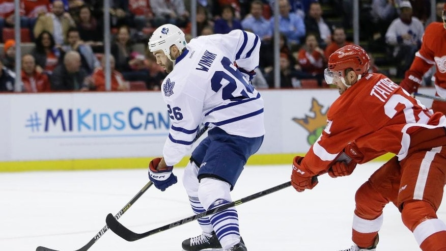 Detroit Red Wings left wing Tomas Tatar (21) of the Czech Republic slashes Toronto Maple Leafs right wing Daniel Winnik (26) during the first period of an NHL hockey game in Detroit, Wednesday, Dec. 10, 2014. (AP Photo/Carlos Osorio)