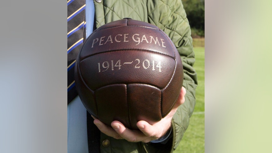 In this photo taken on Sunday, Aug. 24, 2014 an organizer holds a period soccer ball prior to the start of a Christmas Truce Peace Game soccer match between British team Newark Town FC and German team FC Emmendingen in Messines, Belgium. Britain's Newark Town FC and Germany's FC Emmendingen participated in a Peace Game to commemorate a spontaneous truce which happened along the front lines during World War I. (AP Photo/Virginia Mayo)