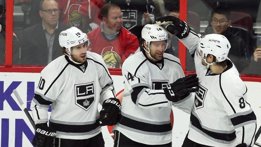Los Angeles Kings' Justin Williams (14) celebrates his goal against the Ottawa Senators with teammates Mike Richards (10) and Drew Doughty (8) during the second period of an NHL hockey game, Thursday, Dec. 11, 2014 in Ottawa. (AP Photo/The Canadian Press, Fred Chartrand)