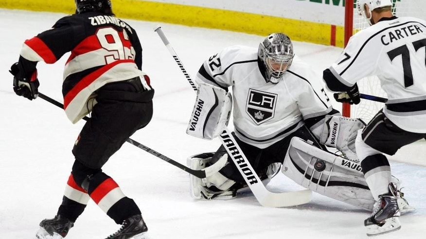 Los Angeles Kings goaltender Jonathan Quick (32) makes a save on Ottawa Senators' Mika Zibanejad (93) as Kings' Jeff Carter looks on during the first period of an NHL hockey game, Thursday, Dec. 11, 2014 in Ottawa. (AP Photo/The Canadian Press, Fred Chartrand)