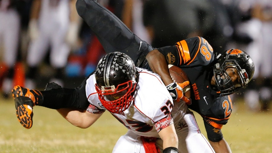 Nov. 28, 2014:  Douglass High School's Anthony Jackson (28) is brought down by Locust Grove High School's Vance Wilson during a their Class 3A high school football quarterfinal playoff game in Oklahoma City.