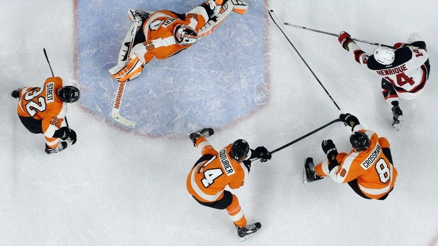 Philadelphia Flyers' Ray Emery (29) blocks a shot by New Jersey Devils' Adam Henrique (14) as Nicklas Grossmann (8), of Sweden, Sean Couturier (14) and Mark Streit (32), of Switzerland, defend during the first period of an NHL hockey game, Thursday, Dec. 11, 2014, in Philadelphia. (AP Photo/Matt Slocum)