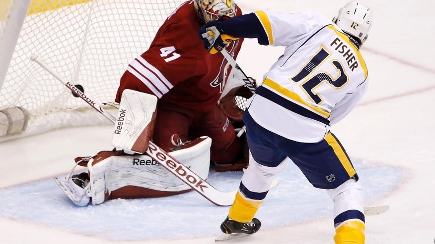 Nashville Predators' Mike Fisher (12) scores a goal against Arizona Coyotes' Mike Smith (41) during the first period of an NHL hockey game Thursday, Dec. 11, 2014, in Glendale, Ariz. (AP Photo/Ross D. Franklin)