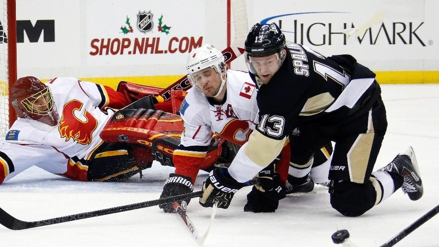 Pittsburgh Penguins' Nick Spaling (13) and Calgary Flames' Kris Russell (4) collide in front of Flames goalie Jonas Hiller (1) during the second period of an NHL hockey game in Pittsburgh, Friday, Dec. 12, 2014.(AP Photo/Gene J. Puskar)