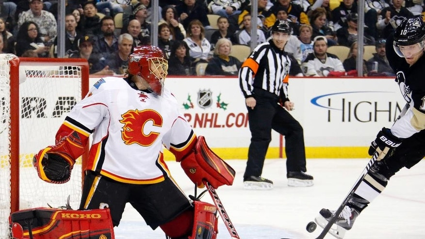Pittsburgh Penguins' Christian Ehrhoff (10) can't get a shot off in front of Calgary Flames goalie Jonas Hiller (1) during the second period of an NHL hockey game in Pittsburgh, Friday, Dec. 12, 2014. (AP Photo/Gene J. Puskar)