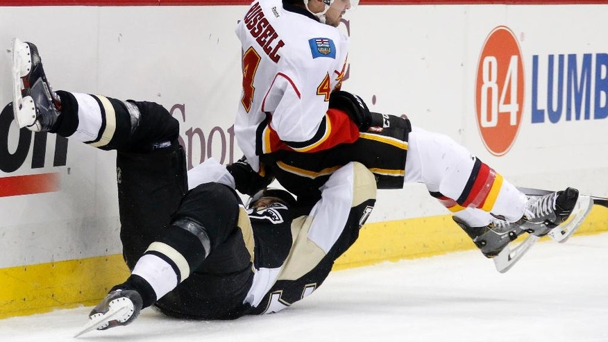 Calgary Flames' Kris Russell (4) collides with Pittsburgh Penguins' Evgeni Malkin (71) during the second period of an NHL hockey game in Pittsburgh Friday, Dec. 12, 2014.(AP Photo/Gene J. Puskar)