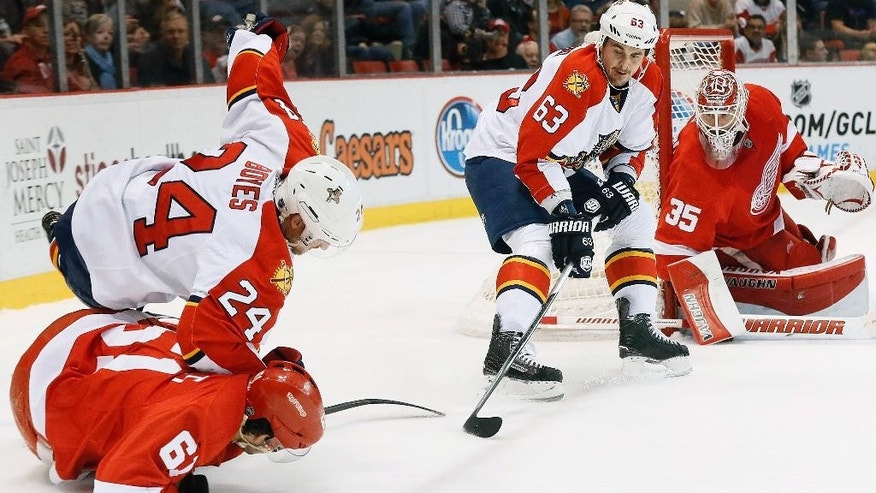 Florida Panthers center Dave Bolland (63) skates with the puck as Florida Panthers right wing Brad Boyes (24) and Detroit Red Wings Xavier Ouellet collide in the first period of an NHL hockey game in Detroit, Friday, Dec. 12, 2014. (AP Photo/Paul Sancya)