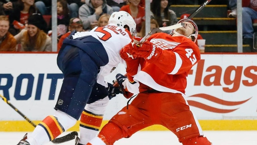 Florida Panthers defenseman Aaron Ekblad (5) hits Detroit Red Wings center Darren Helm (43) with a high stick in the second period of an NHL hockey game in Detroit Friday, Dec. 12, 2014. (AP Photo/Paul Sancya)