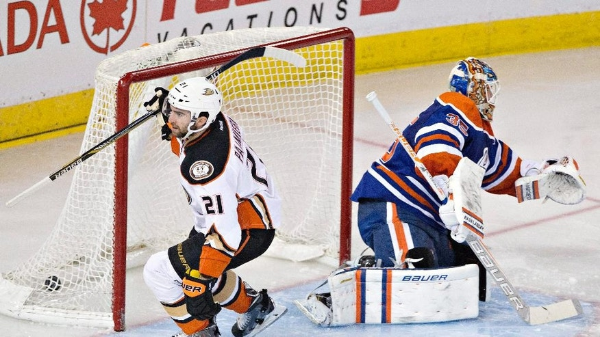 Anaheim Ducks' Kyle Palmieri (21) scores a goal against Edmonton Oilers goalie Viktor Fasth (35) during the second period of their NHL hockey game in Edmonton, Alberta, Canada on Friday, Dec. 12, 2014. (AP Photo/The Canadian Press, Jason Franson)