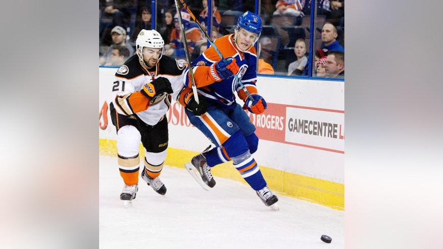 Anaheim Ducks' Kyle Palmieri (21) and Edmonton Oilers' Mark Fayne (5) battle for the puck during the first period of their NHL hockey game in Edmonton, Alberta, Canada on Friday, Dec. 12, 2014. (AP Photo/The Canadian Press, Jason Franson)