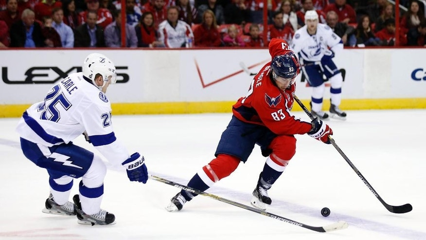 Washington Capitals center Jay Beagle (83) skates with the puck as Tampa Bay Lightning defenseman Matt Carle (25) defends, in the second period of an NHL hockey game, Saturday, Dec. 13, 2014, in Washington. (AP Photo/Alex Brandon)