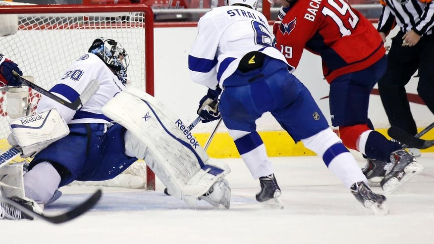 Washington Capitals center Nicklas Backstrom (19), from Sweden, scores his second goal past Tampa Bay Lightning goalie Ben Bishop (30) and defenseman Anton Stralman (6), from Sweden, in the second period of an NHL hockey game, Saturday, Dec. 13, 2014, in Washington. (AP Photo/Alex Brandon)