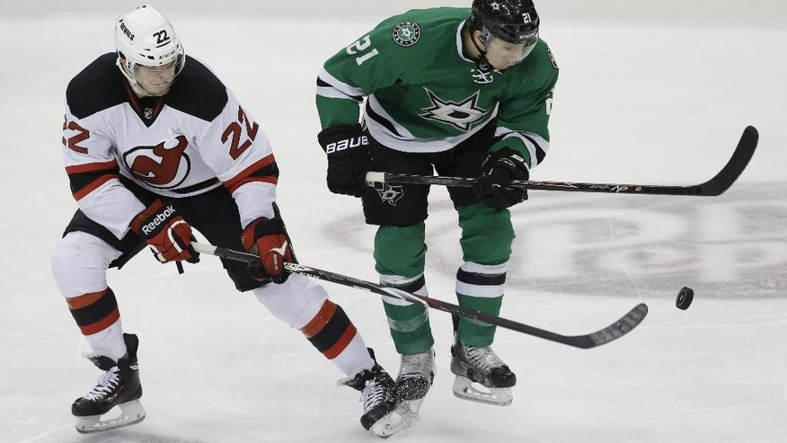 New Jersey Devils defenseman Eric Gelinas (22) and Dallas Stars left wing Antoine Roussel (21) skate for the puck during the third period of an NHL hockey game Saturday, Dec. 13, 2014, in Dallas. The Stars won 4-3. (AP Photo/LM Otero)
