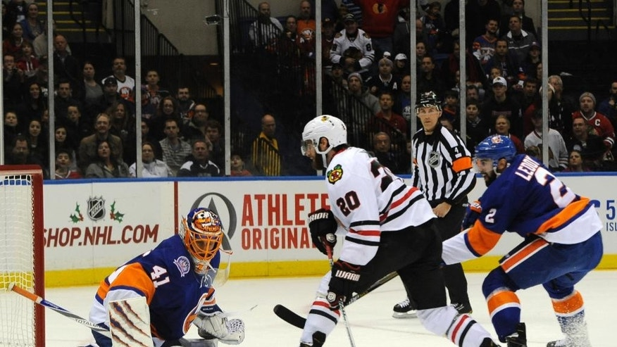 New York Islanders goalie Jaroslav Halak (41) blocks a shot on goal by Chicago Blackhawks left wing Brandon Saad (20) as Islanders defenseman Nick Leddy (2) defends in the first period of an NHL hockey game on Saturday, Dec. 13, 2014, in Uniondale, N.Y. (AP Photo/Kathy Kmonicek)