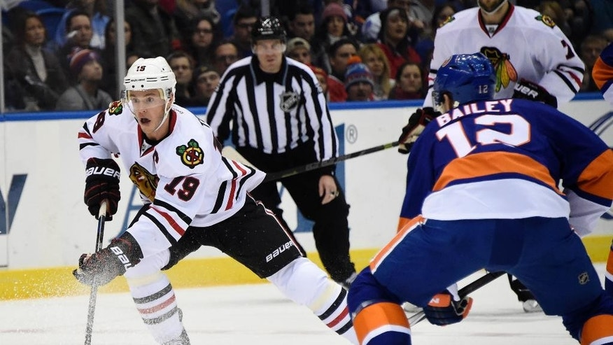 Chicago Blackhawks center Jonathan Toews (19) drives the puck downice past New York Islanders left wing Josh Bailey (12) in the first period of an NHL hockey game on Saturday, Dec. 13, 2014, in Uniondale, N.Y. (AP Photo/Kathy Kmonicek)