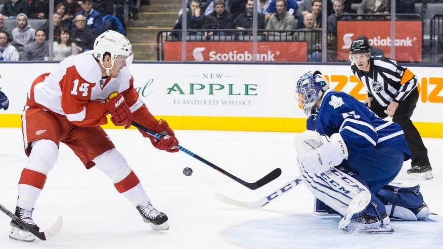 Toronto Maple Leafs goaltender Jonathan Bernier, right, saves a shot from Detroit Red Wings' Gustav Nyquist during first period of an NHL hockey game in Toronto, Saturday, Dec. 13, 2014. (AP Photo/The Canadian Press, Chris Young)