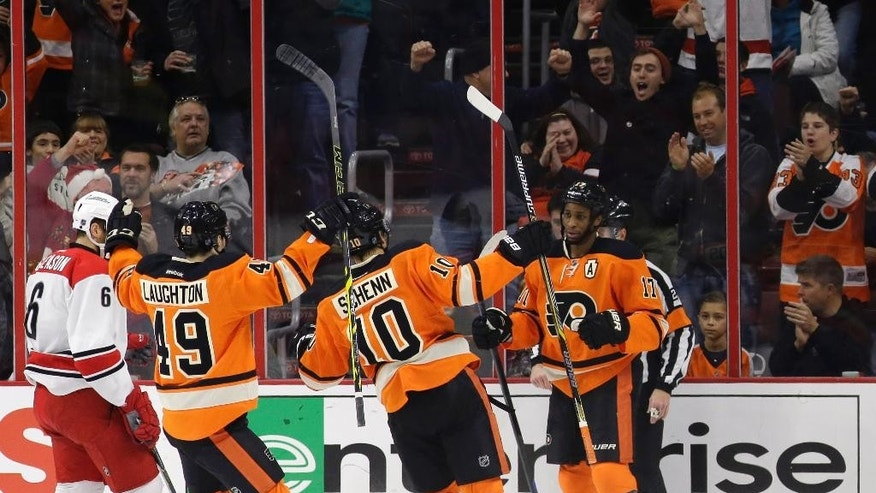 Philadelphia Flyers' Wayne Simmonds (17) celebrates with Brayden Schenn (10) and Scott Laughton (49) after scoring a goal during the first period of an NHL hockey game against the Carolina Hurricanes, Saturday, Dec. 13, 2014, in Philadelphia. (AP Photo/Matt Slocum)