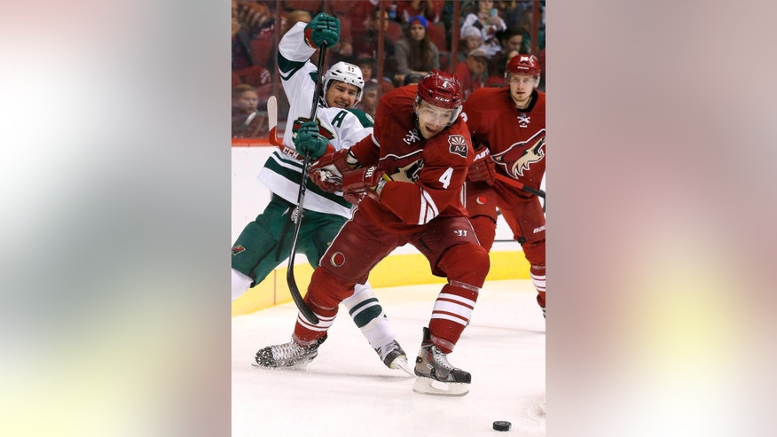 Arizona Coyotes' Zbynek Michalek (4), of the Czech Republic, gets tangled up with Minnesota Wild's Zach Parise, left, during the first period of an NHL hockey game Saturday, Dec. 13, 2014, in Glendale, Ariz. (AP Photo/Ross D. Franklin)