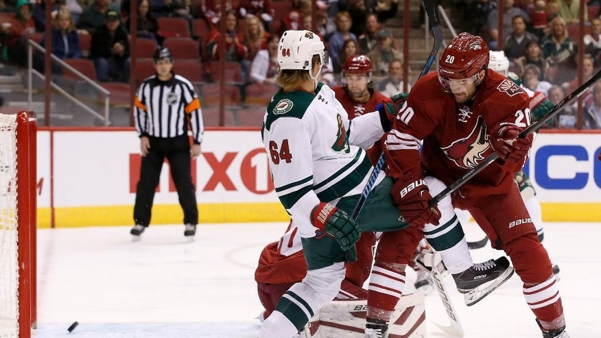 As Arizona Coyotes' Chris Summers (20) battles with  Minnesota Wild's Mikael Granlund (64), of Finland, the puck shot by Wild's Nino Niederreiter goes into the net for a goal during the first period of an NHL hockey game Saturday, Dec. 13, 2014, in Glendale, Ariz. (AP Photo/Ross D. Franklin)