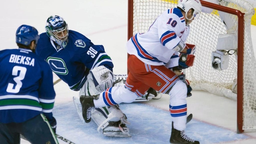 Vancouver Canucks defenseman Kevin Bieksa (3) looks on as New York Rangers center J.T. Miller (10) puts a shot past Vancouver Canucks goalie Ryan Miller (30) during the first period of an NHL hockey game, Saturday, Dec. 13, 2014 in Vancouver, British Columbia. (AP Photo/The Canadian Press, Jonathan Hayward)