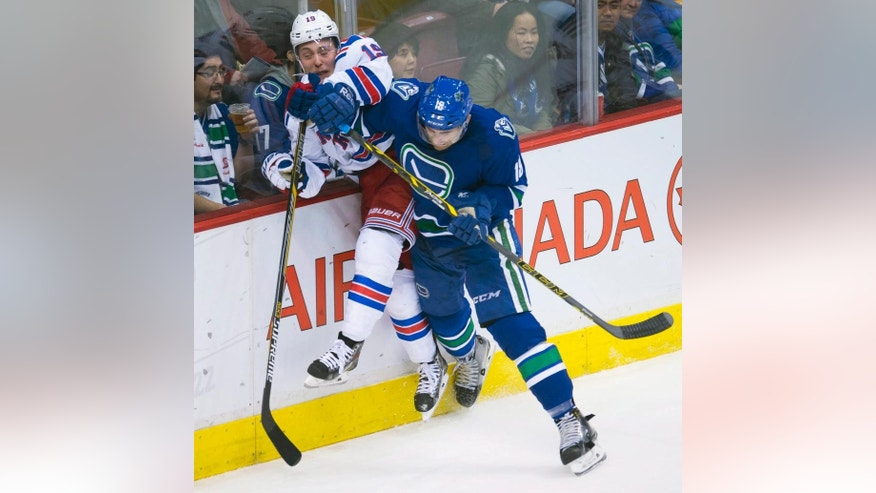 Vancouver Canucks defenseman Ryan Stanton (18) goes into the boards with New York Rangers right wing Jesper Fast (19) during the second period of an NHL hockey game, Saturday, Dec. 13, 2014 in Vancouver, British Columbia. (AP Photo/The Canadian Press, Jonathan Hayward)
