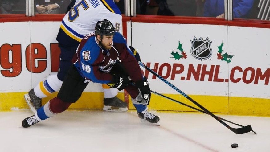Colorado Avalanche center Ryan O'Reilly, front, reaches out to control the puck as St. Louis Blues defenseman Barret Jackman covers in the third period of an NHL hockey game on Saturday, Dec. 13, 2014, in Denver. The Blues won 3-2 in overtime. (AP Photo/David Zalubowski)