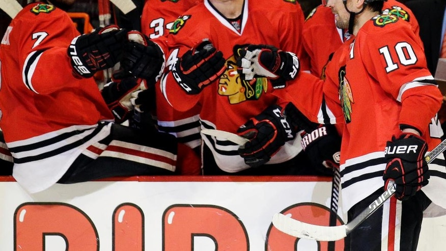 Chicago Blackhawks left wing Patrick Sharp (10) celebrates with teammates after scoring his goal during the second period of an NHL hockey game against the Calgary Flames in Chicago, Sunday, Dec. 14, 2014. (AP Photo/Nam Y. Huh)
